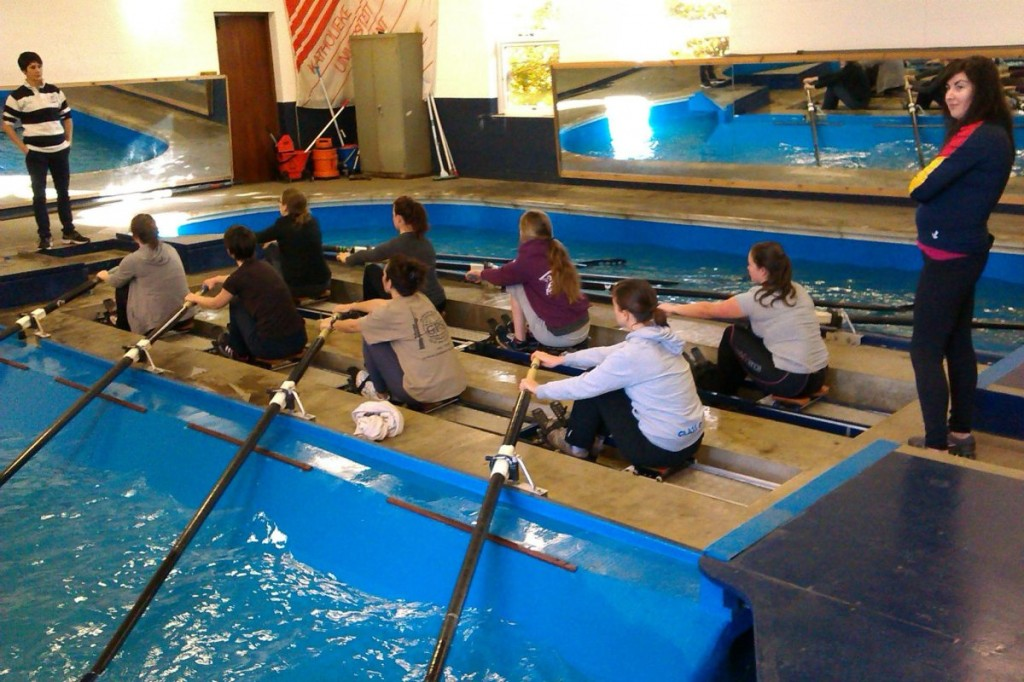 "Novice rowers participate in an indoor ""tank session"", learning finer points of the stroke."